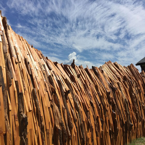 A sideview of the ragged ridgleline of this tunnel-like sculpture made of vertical wood pieces. Behind the sculpture is a sunny sky with wispy clouds.