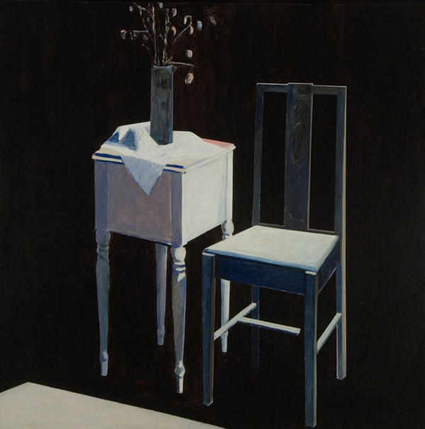 A spare white wooden table and chair, lit from the back right, sit on a black background. On the table, on top of a crumple white cloth, sits a vase with a few stalks of seedpods inside it.