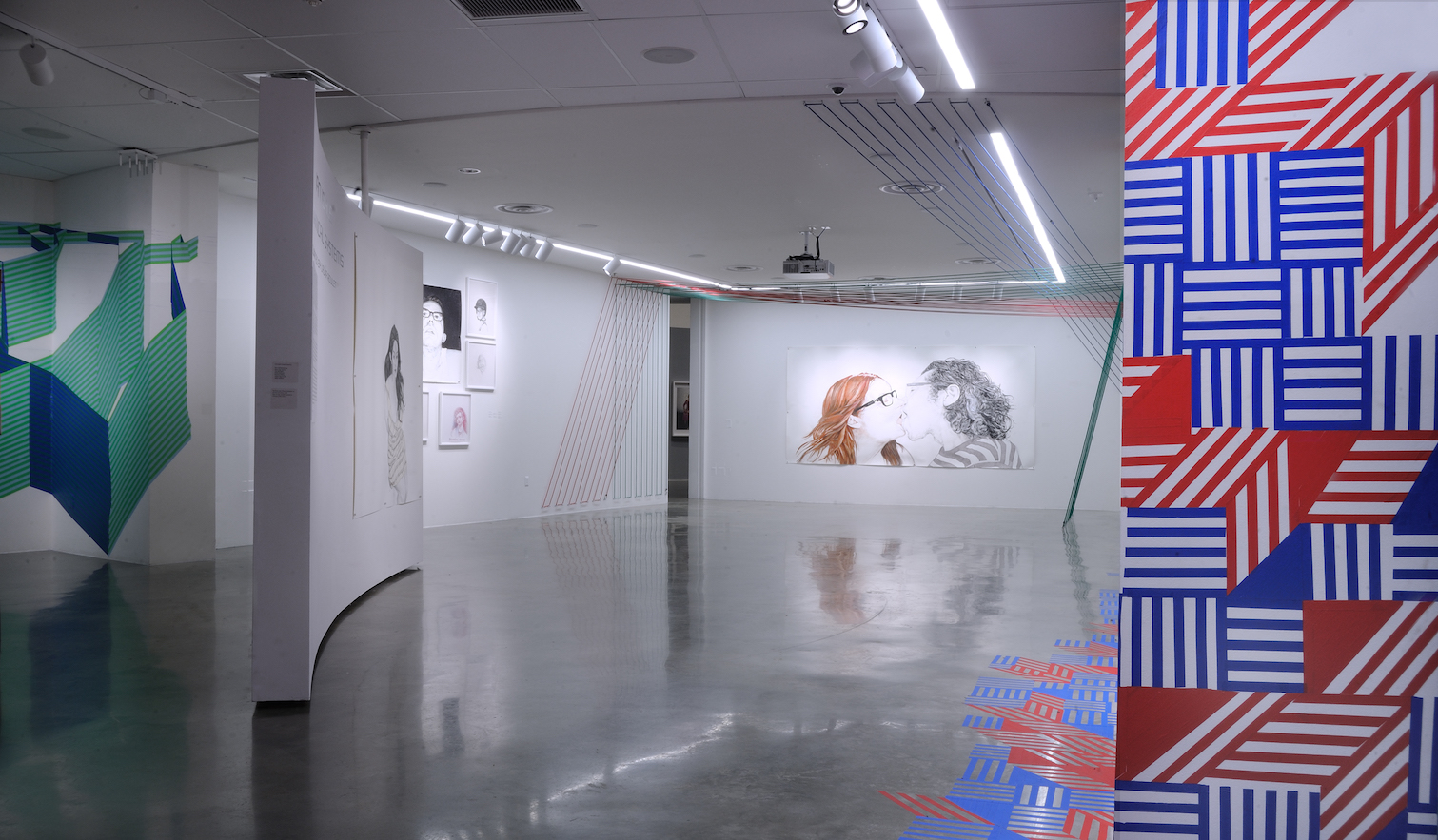 Installation view of multimedia exhibition with portraiture and bungee cords
