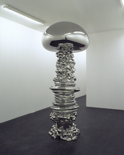 A large silver sculpture. Stacked on the bottom with a mushroom like top.
