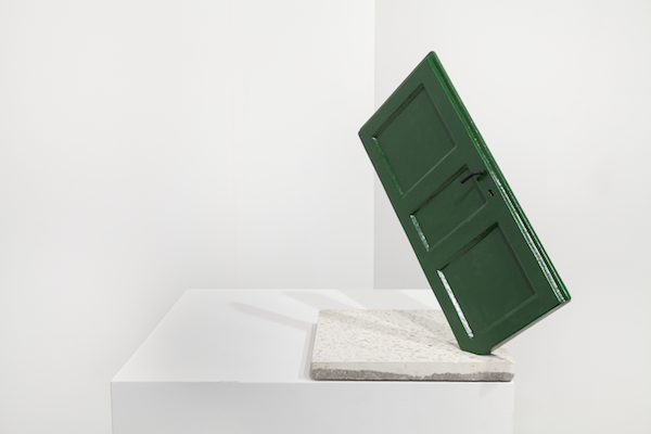A green door is stuck in a white granite block.