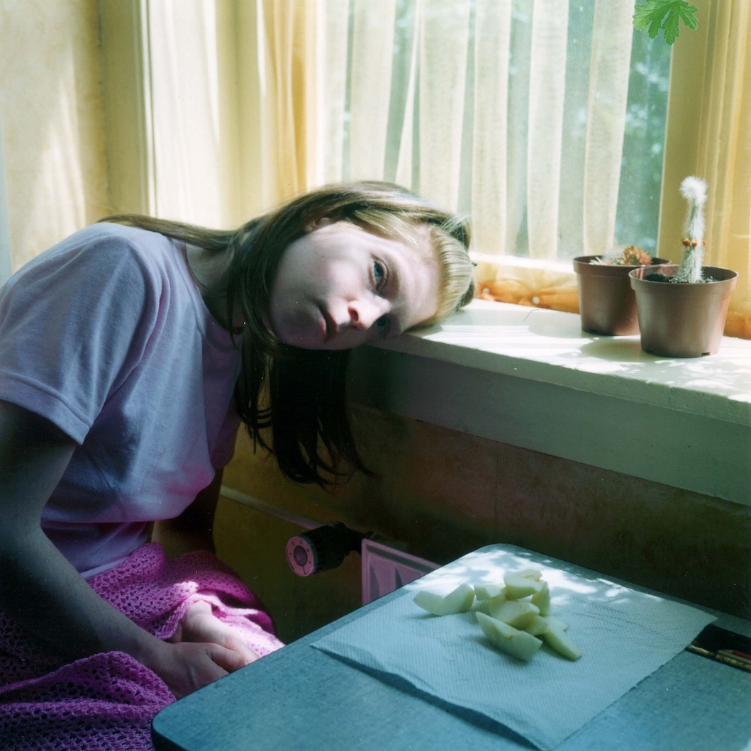 A young woman in an interior, leaning her head on a windowsill looking at the camera