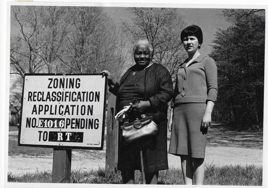 Two women and a sign saying 'Zoning Reclassfication Application NO. E106 Pending'