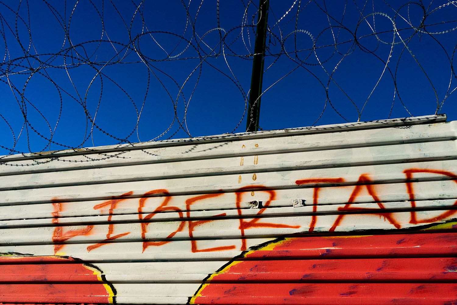 "Border wall with graffitied text ""libertad"""