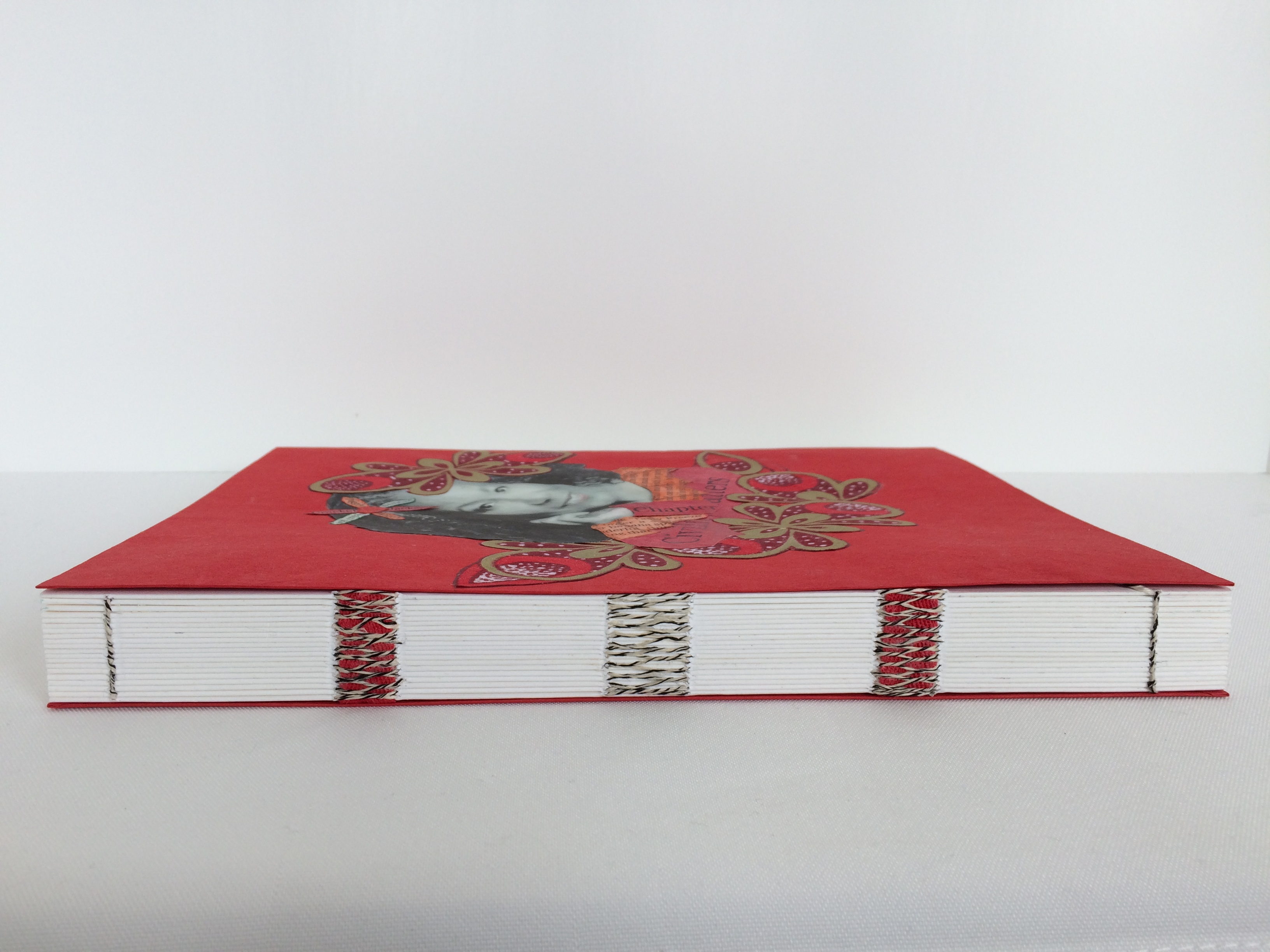 A side view of a red handmade book with a woman's photograph on the front