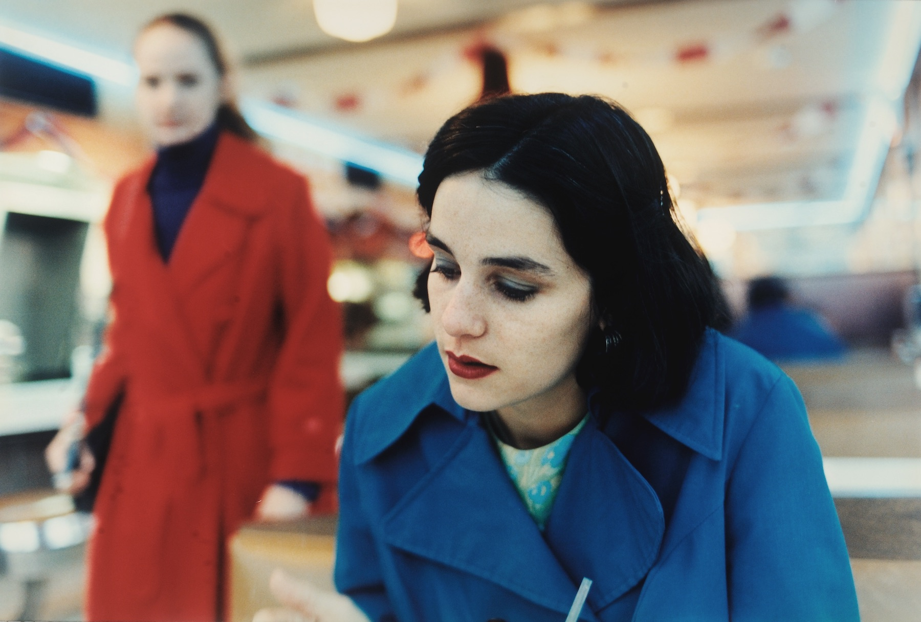 Two women, in blue and red coats