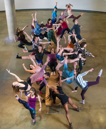 Photo from above of 22 dance students leaning joyfully out from a bench in the center of the shot.