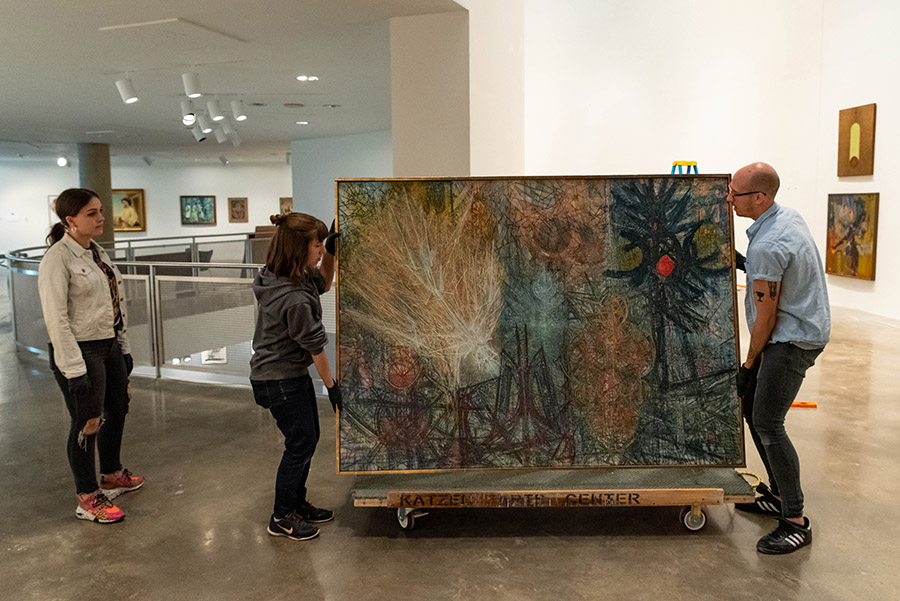 Three people move one of the pieces of art from a cart