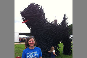 Photo of Kathy Franz near a wooden Hungarian Puli at the 2013 festival.