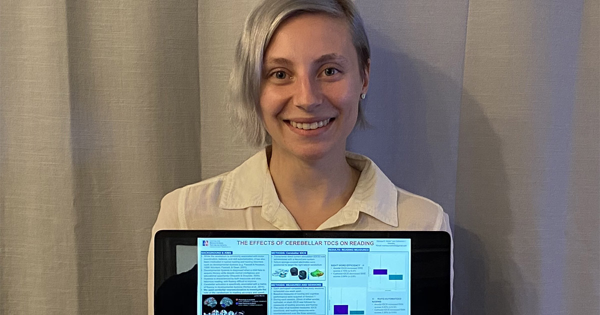 A student poses with a laptop that is displaying their research poster