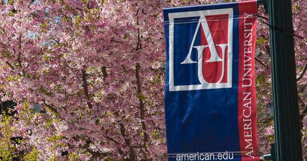 AU pennant in front of cherry blossom trees