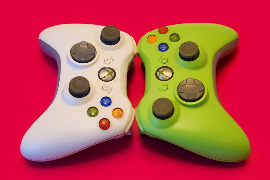 Two video game controllers face each other on a red background.