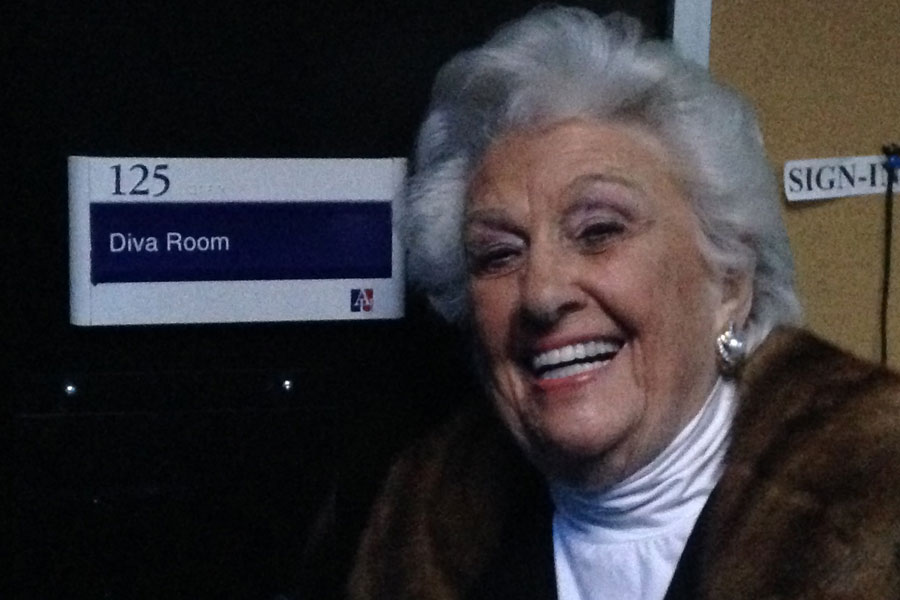 Sylvia Greenberg outside a door labelled 'Diva Room'