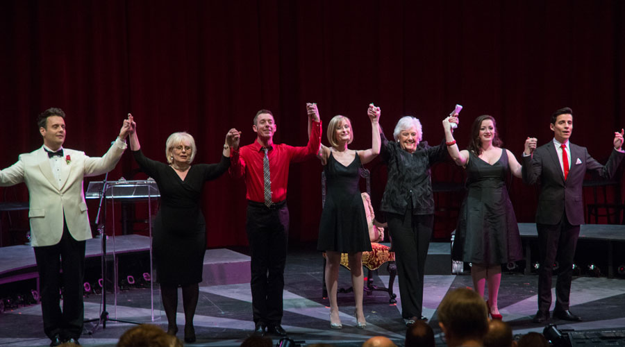 Sylvia Greenberg clasps hands in a line of performers on stage