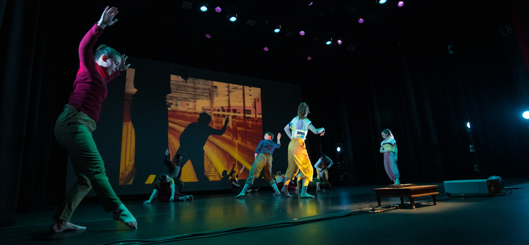 Dancers perform with projection of abstract images behind them, at the Greenberg Theatre