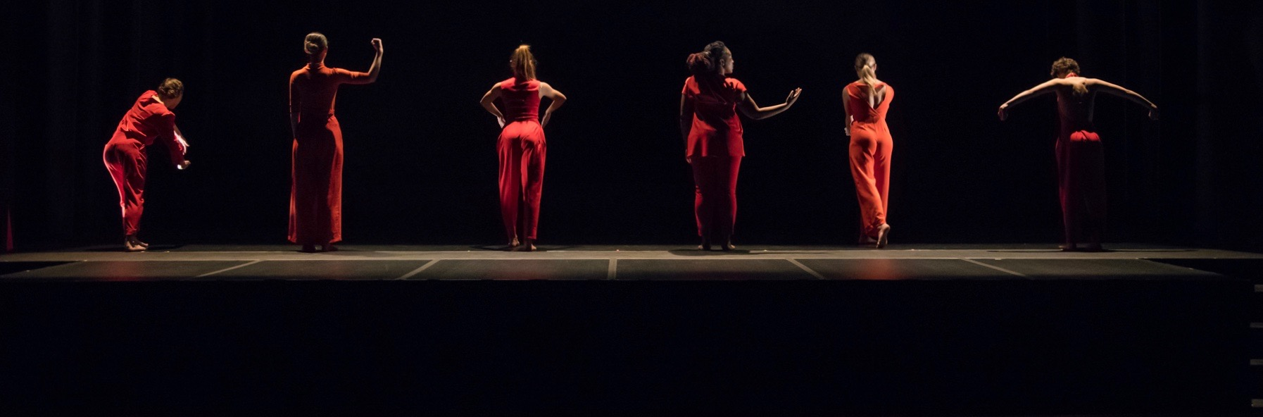 Dancers stand in a line, dressed in red, gesturing towards upstage