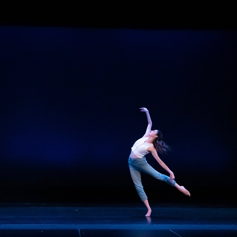 Dancer balances on one foot, limbs outstretched