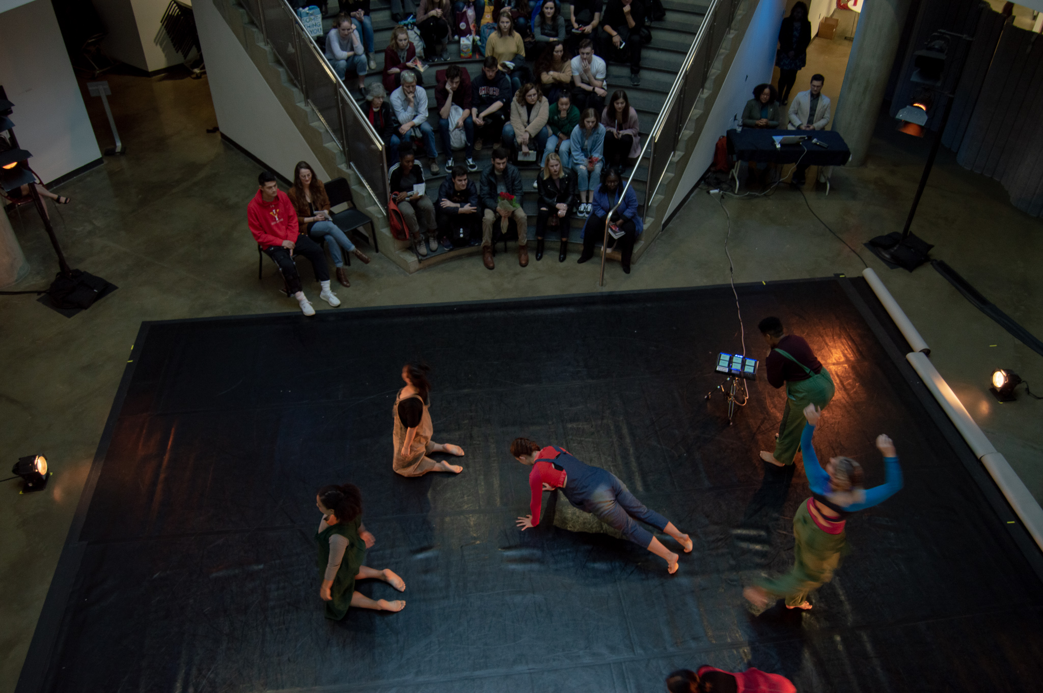 Audience sits on the steps of the Katzen Rotunda watching dancers perform.