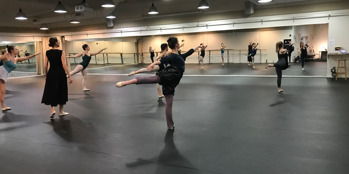 Students stand in arabesque in the dance studio
