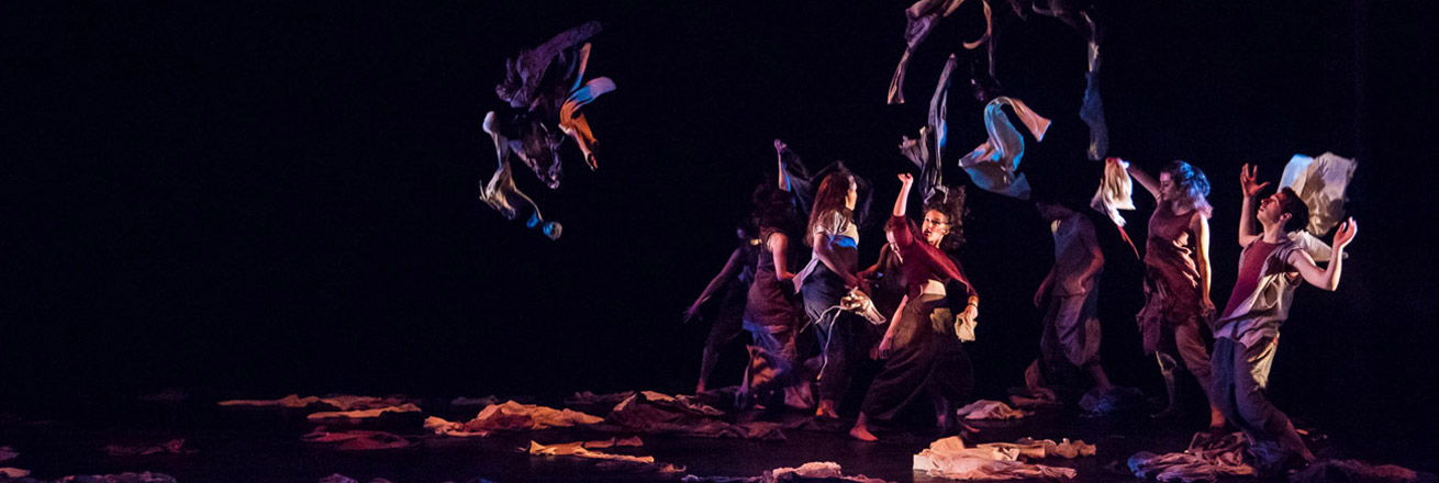 Dancers toss bundles of clothes into the air