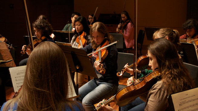 Students practice the violin.