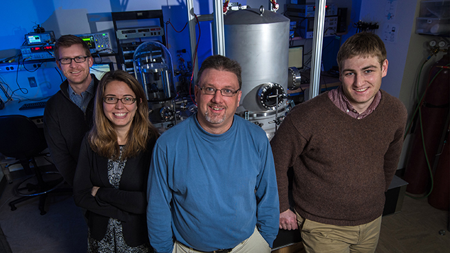 Four smiling scientists stand in a lab lit with blue light