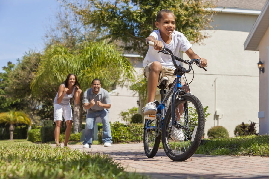 Child zooms past on bike as parents cheer