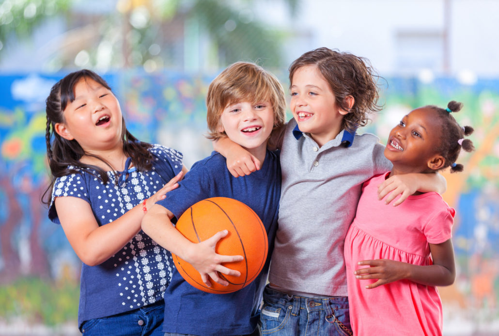 Laughing children gather around a basketball