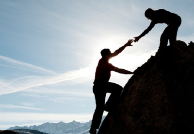 Silhouette of one person lending a hand to help another up a mountain