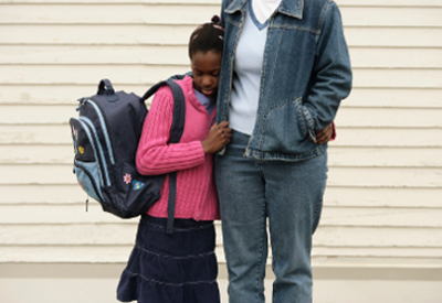 A child holding a backpack clutches a parent's side,