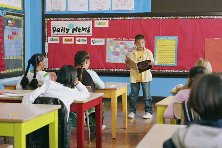 Child stands at front of classroom, reading a book aloud