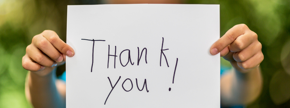 "A child's hands hold a paper saying ""Thank You"""