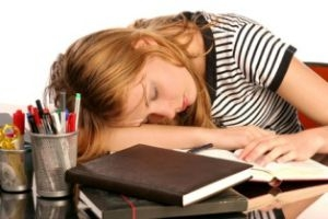 Teen sleeping at classroom desk