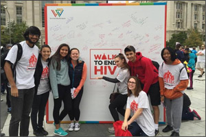 Students in front of sign that says Walk to End HIV