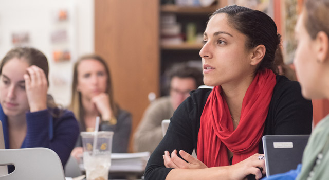Student in red scarf looks contemplative in class