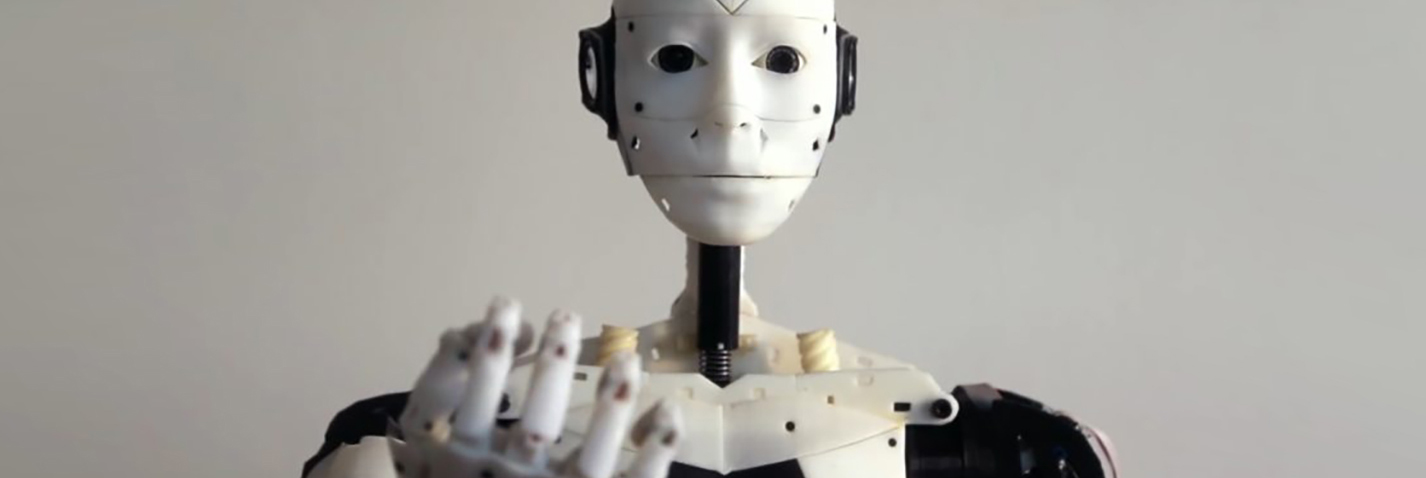 A closeup of a robot's face with an outstretched hand.