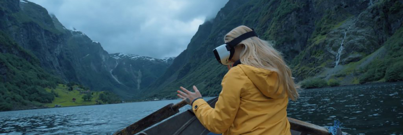 A woman in a VR headseat overlooking the water on a boat.