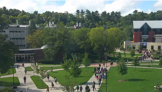 Students walk to class across a wide quad.