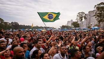 Large crowd of people holding a Brazilian flag