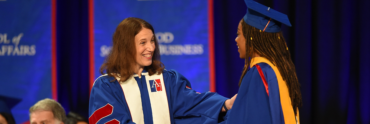 President Burwell shaking hands with graduate
