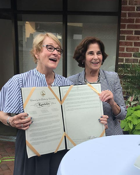 Linda Argo (left), holding the resolution presented to her from the D.C. government, by Mary Cheh (right)