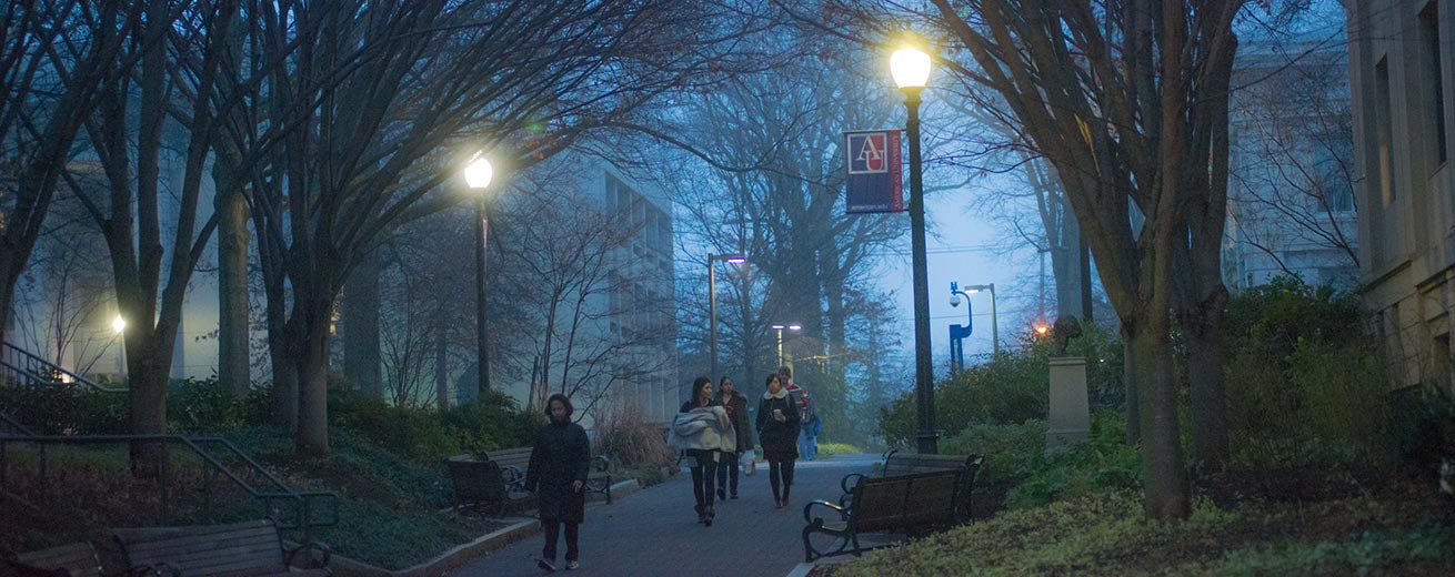 Students walking on campus at dusk