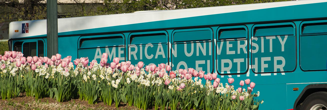 Shuttle bus on campus in spring, with tulips in foreground