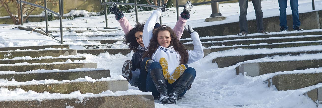 Students sledding at the amphitheater