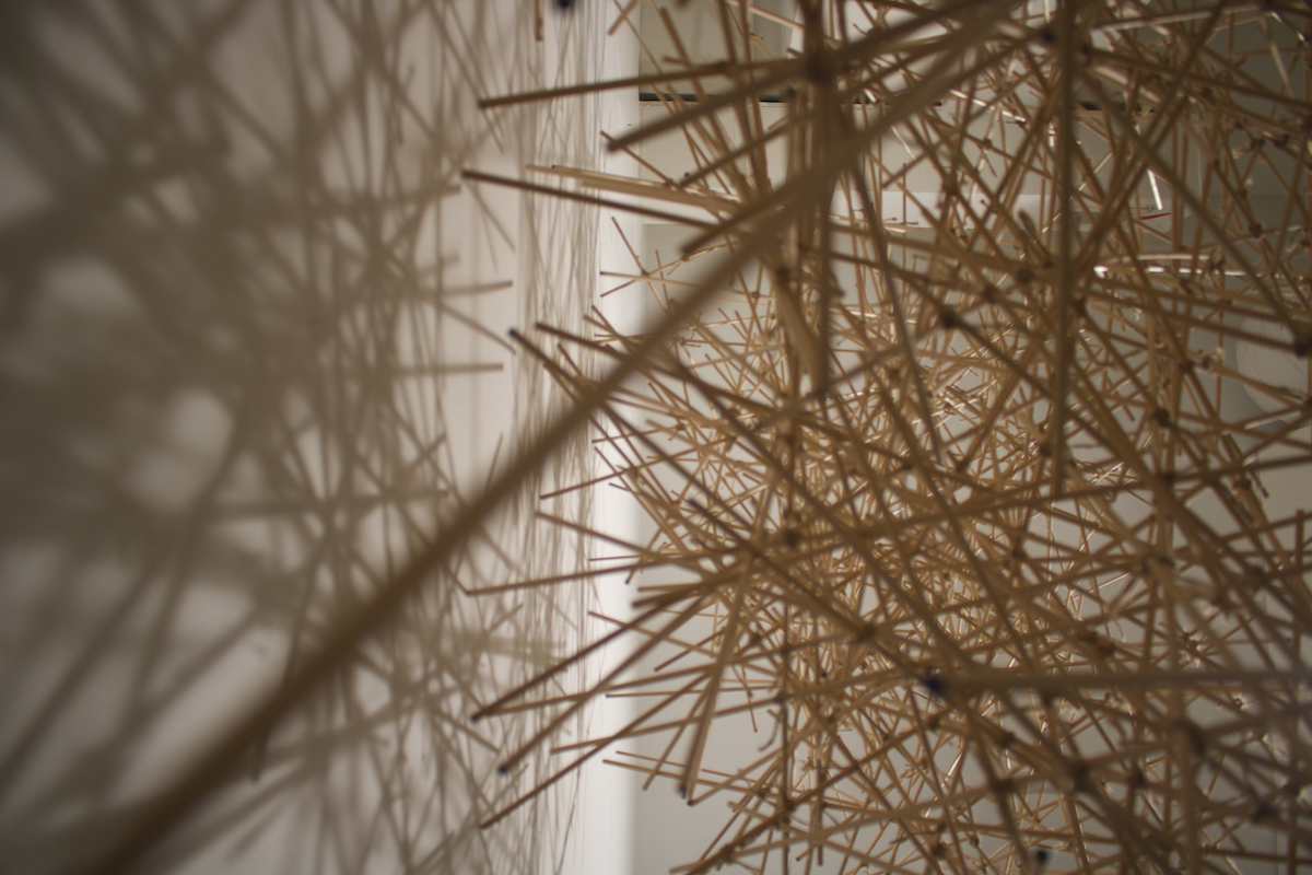 Closeup of Jennifer Frank's installation art, Rodified, made of birch dowels and twine.