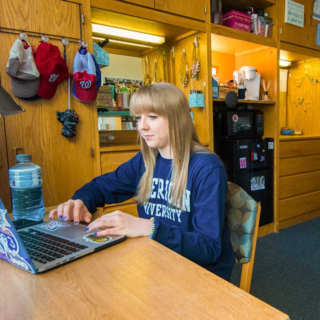 A first-year student at her desk in her room in Anderson Hall.