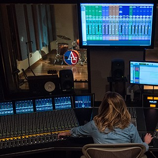 An audio technology student mixes music using American University's state-of-the art equipment.