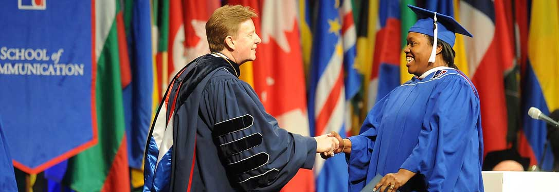 Photo of AU President Neil Kerwin shaking hands with masters degree recipient