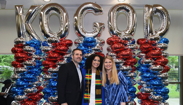 A graduate and her family pose in front of balloons spelling KOGOD