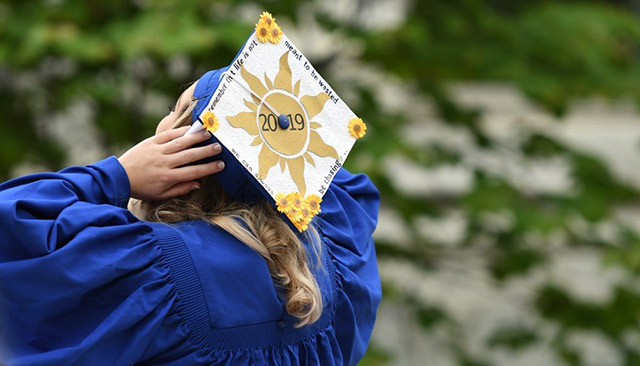 A graduate shows off her decorated cap